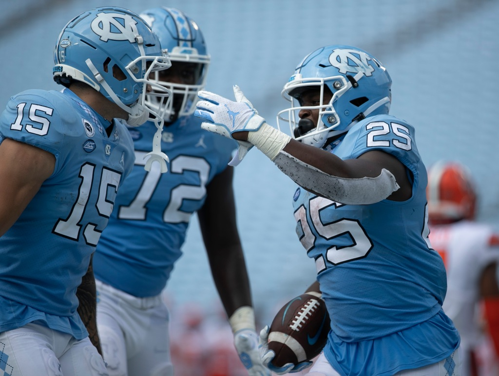 North Carolina's Javonte Williams (25) celebrates with teammates after scoring a touchdown to give the Tar Heels' a 24-6 lead in the fourth quarter against Syracuse on Saturday.